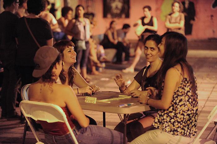 Cuatro jóvenes se disfrutan un juego de dominó