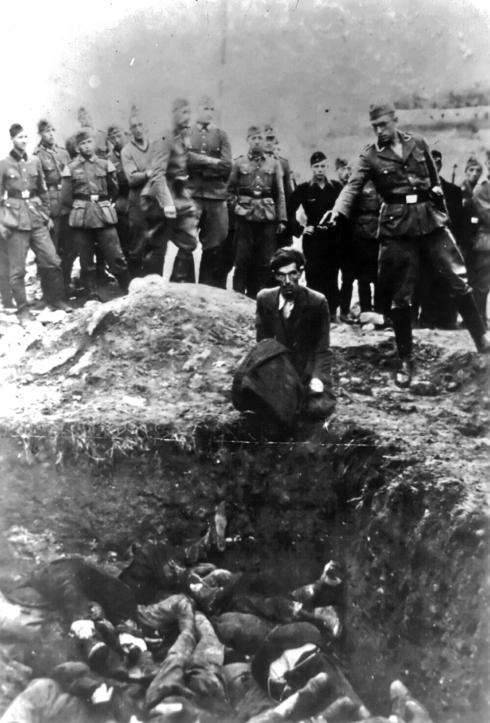 Un miembro del Einsatzgruppe D se prepara para dispararle a un hombre sentado a la orilla de una fosa común en Vinnytsia, Ucrania, durante el Holocausto. Presentes en el fondo se encuentran miembros del ejército alemán, del servicio laboral alemán y las juventudes hitlerianas. (Suministrada).
