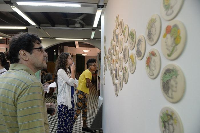 Espectadores han venido a buscarse entre los retratos o identificar retratos de personas conocidas. (Ricardo Alcaraz/Diálogo)