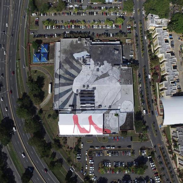 Imagen de la pieza del dúo frances Ella & Pitr, que forma parte de su serie 'Gigantes dormidos'. La misma presenta a un pequeño bebé durmiendo tranquilamente con su cansada madre a su lado, hecha en el techo de un edificio en Santurce. (Facebook/SanturceEsLey)