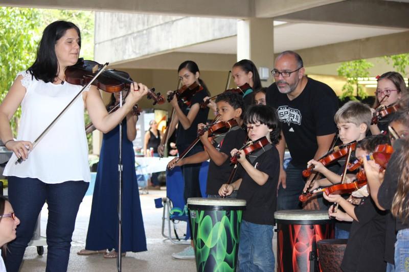 """Los niños de la Asociación Suzuki de violinistas de Puerto Rico interpretan un número musical como parte de su narración del cuento """"El flamboyán amarillo""""."""