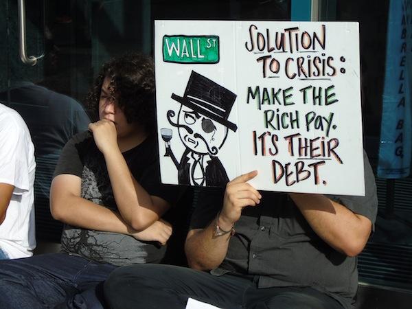 """Dice el cartel: """"Solución a la crisis: hacer que los ricos paguen. Es su deuda"""". (Perla Rodríguez - Diálogo)"""