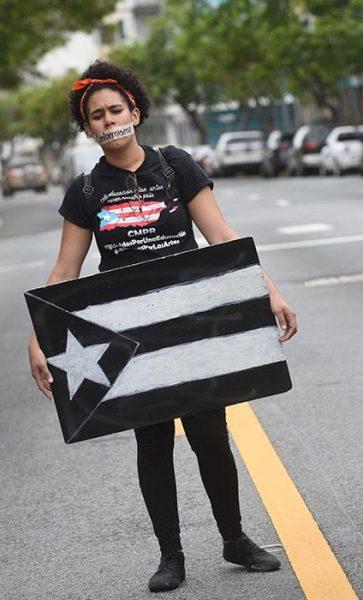 Una universitaria cargó una bandera puertorriqueña en luto, mientras una cinta adhesiva con la palabra 'conformismo' inscrita cubrió sus labios. (Ricardo Alcaraz/Diálogo)
